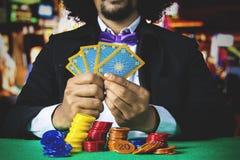 Hasardspelaren rymmer pokerkort Arkivfoto