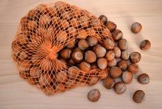 Haselnüsse auf einem Holztisch und einem Netz Stockbild