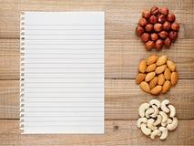 Haselnüsse, Mandeln, Acajounüsse und Papier für Rezept Stockbild
