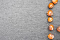 Haselnussnüsse Beschneidungspfad eingeschlossen auf einem Schieferteller Kopieren Sie Raum auf dem links lizenzfreie stockbilder