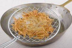 Hash brown is taken out of a frying pan Stock Image
