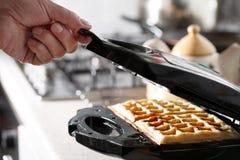 Hash - Browns που γίνεται στην αμυχή κουζινών κατασκευαστών βαφλών Στοκ φωτογραφία με δικαίωμα ελεύθερης χρήσης