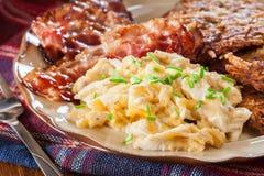 Hash - Browns Τηγανίτες πατατών με το τριζάτο τηγανισμένο μπέϊκον και τα ανακατωμένα αυγά Στοκ φωτογραφίες με δικαίωμα ελεύθερης χρήσης