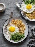 Hash - Browns, τηγανισμένα αυγό και arugula στο γκρίζο υπόβαθρο, τοπ άποψη Στοκ Φωτογραφίες