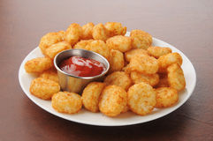 Hash browns and catsup. A plate of hash browns potato cakes with catsup royalty free stock image