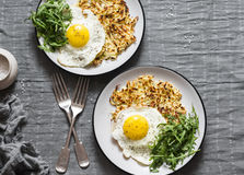 Hash Browns, fried egg and arugula on grey background, top view. Delicious simple lunch stock images