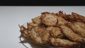 Hash browns with Golden crust on a plate camera moves from left to right. Cooking stock video