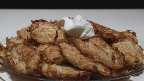 On hash browns with a golden crust put sour cream on a plate the camera is static slowmotion. Cooking stock footage