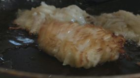 Hash browns are turned over with a spatula on a frying pan stock video