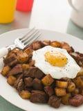 Hash di corned beef con un uovo fritto e un pepe nero Immagine Stock Libera da Diritti