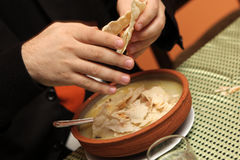 Hash soup. A man crumbles dry lavash into Hash soup - Armenian National dish royalty free stock images