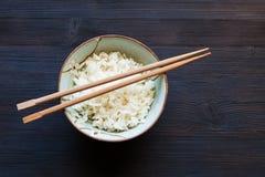 Hashis acima do arroz fervido na bacia na tabela escura foto de stock