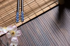 Hashis do sushi na tabela de bambu com sukura Fotografia de Stock