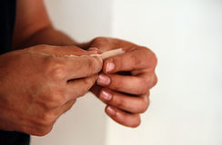 Hashish joint. Close up of male hand rolling hashish joint Royalty Free Stock Photos