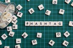 Hashtag词由方形的信件词制成在绿色方形的席子背景 免版税库存图片