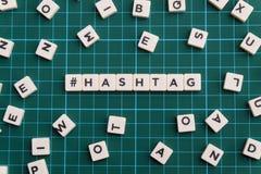 Hashtag词由方形的信件词制成在绿色方形的席子背景 免版税图库摄影