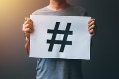 Hashtag as viral web social media network concept. For marketing, trending, blogging and internet themes. Man holding paper with hash tag symbol Stock Images