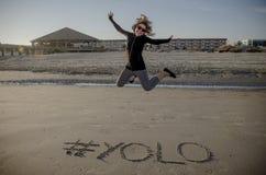Hashtag de YOLO écrit dans le sable sur la plage et sauter de femelle adulte photographie stock libre de droits