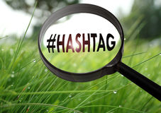 Hashtag. Magnifying glass with the word hashtag on grass background. Selective focus Royalty Free Stock Image