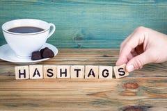 Hashtags Träbokstäver på den informativ och kommunikationsbakgrunden för kontorsskrivbord, royaltyfria bilder