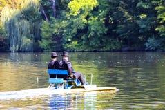 2 Hasidic Jews ride a catamaran on the lake in the autumn Park in Uman, Ukraine, during the Jewish New Year. Rosh-ha-shana stock photos