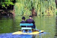 2 Hasidic judar i traditionell svart kläder rider en katamaran på sjön i hösten Sophia Park i Uman, Ukraina, royaltyfri foto