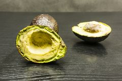 Hass avocado Bilse avocado. Cut in half Hass avocado on a wooden dark table Stock Photos