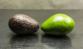Hass and Choquette avocado. Hass and Choquette avocado on a wooden dark table Royalty Free Stock Photo