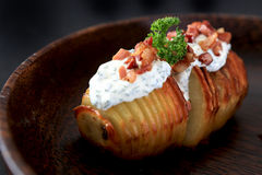 Hasselback potato. Slow roasted potato topping with sour cream, chive, and diced bacon stock images