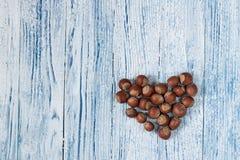 Hasselnöthjärtablått och bakgrund för gammal grunge för whie trä arkivbild