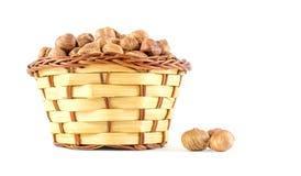Hasselnötter i en träkorg som isoleras på vit Arkivfoton