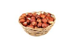 Hasselnötter i korgen som isoleras på vit Royaltyfria Foton