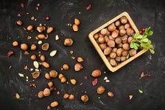 Hasselnötter i nötskal i en bakgrund för träaskgrungemörker Royaltyfria Bilder