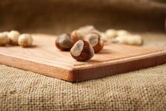hasselnötter i träbunkar på trä och säckväv, säckbakgrund Arkivbilder