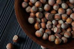 Hasselnötter i träbunke Arkivfoton