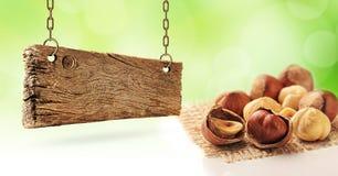 Hasselnötter och träbräde fotografering för bildbyråer