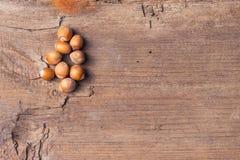 Hasselnötter på en lantlig trätabell abstrakt bakgrund Fotografering för Bildbyråer