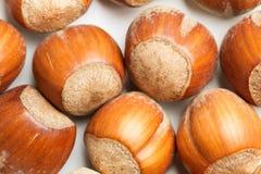 Hasselnötter på en vit tabell Fotografering för Bildbyråer