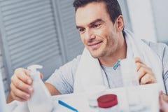 Hasselträ-synad man som tar skönhetsmedel för att raka royaltyfri bild