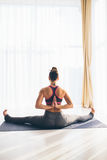 Hastapadasana. Beautiful yoga woman practice in a training hall background. Stock Photos