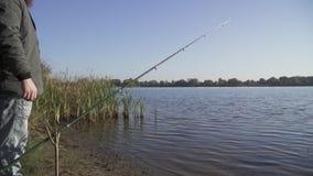 A haste é fixada na vara especial no banco de rio O pescador está próximo e olha a água Pesca do rio lento filme
