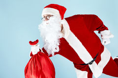 Haste. Photo of happy Santa Claus running with red sack Stock Photos