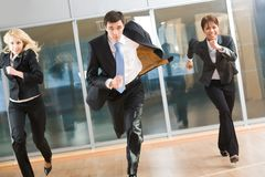 Haste. Portrait of hurrying people in suits running forwards for work with optimistic expression Stock Image