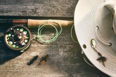 Haste de pesca com mosca com o chapéu na madeira Foto de Stock