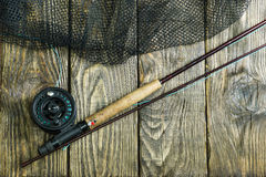 Haste de pesca com mosca, flie e uma rede de aterrissagem na tabela de madeira velha Tudo pronto para pescar fotografia de stock royalty free