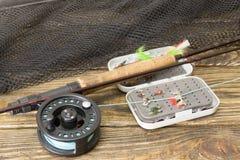 Haste de pesca com mosca, flie e uma rede de aterrissagem na tabela de madeira velha Tudo pronto para pescar fotografia de stock