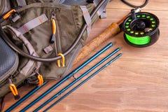 A haste de pesca com mosca com uma bobina e as moscas encontram-se em placas velhas, de madeira imagem de stock