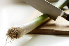 Haste do alho-porro de Cuting com uma faca grande em uma placa de corte de madeira Imagens de Stock Royalty Free