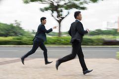 Haste. Two managers running outdoors, blurred motion Royalty Free Stock Photos