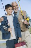 Hastes de pesca da terra arrendada do avô e do neto Imagens de Stock Royalty Free